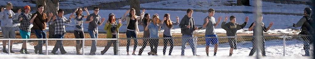 Description of . CENTENNIAL, CO - Students with their arms up are escorted to the football field after being evacuated fro the school. At a about 12:30 pm a student was spotted inside Arapahoe High School carrying a shotgun December 13, 2013. The gunman was targeting a teacher at the school. The gunman shot two students in the process and then turned the gun on himself. DECEMBER 13:  (The Denver Post)