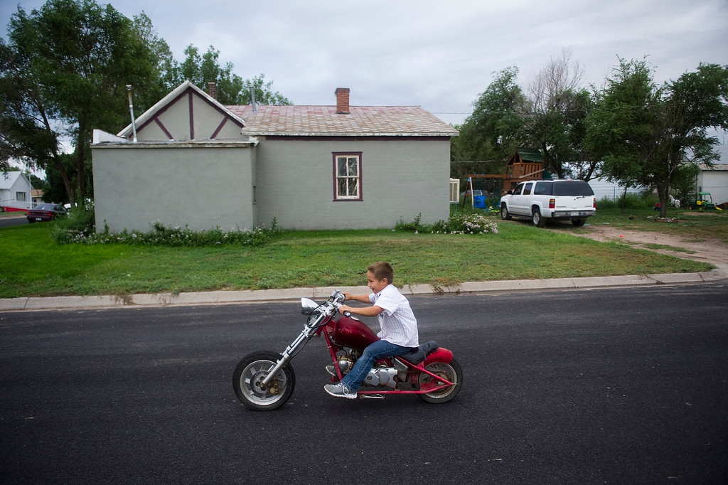 Description of . CHEYENNE WELLS, CO - AUGUST 08, 2013: Ethen Garay, 6, rides his motorcycle past his home on a Thursday evening. The Garay's bought the home for $7000 and fixed it up where they now live with two kids and frequent visitors. (Photo By Grant Hindsley/The Denver Post)