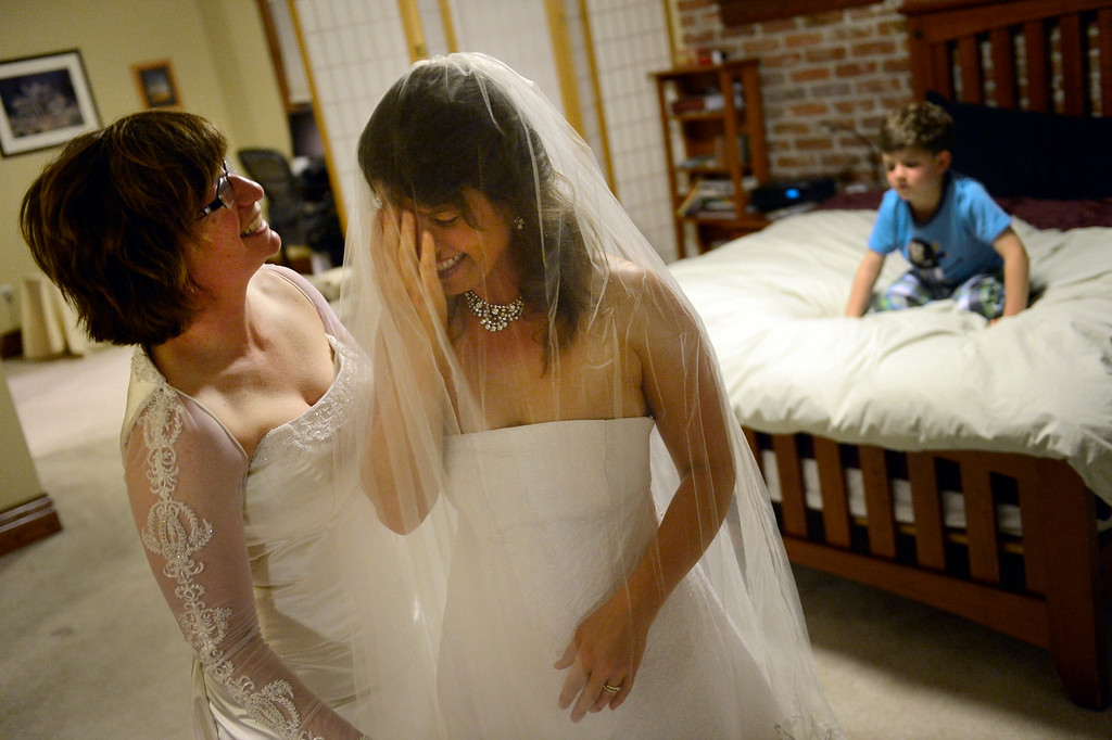 Description of . DENVER, CO. - APRIL 29: Fran, left, and Anna Simon try on their wedding dresses while their son Jeremy, 5, watches from the bed at their home in Denver, CO April 29, 2013. The couple hope to be one of the first in Colorado to be joined in Civil Union just after midnight on May 01, 2013 when the Civil Union Act takes effect. The couple has been together 10 years and wore the same dresses in 2005 when they had a wedding ceremony at the Denver Botanical Gardens. (Photo By Craig F. Walker/The Denver Post)