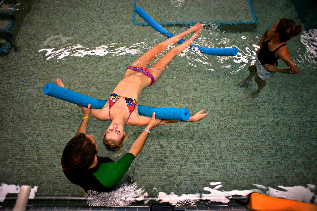 "Description of . ENGLEWOOD, CO. - AUGUST 09:  Karen Gorden said her daughter, Mackenzie, loved the pool workouts because of the freedom, and the chance to more closely approximate walking at Craig Hospital in Englewood, CO August 09, 2013. ""Gravity is not working against her,"" Karen said. Exercise specialist TC Doyle worked with Mackenzie on loosening her hips and arching to strengthen abdominal muscles. (Photo By Craig F. Walker / The Denver Post)"