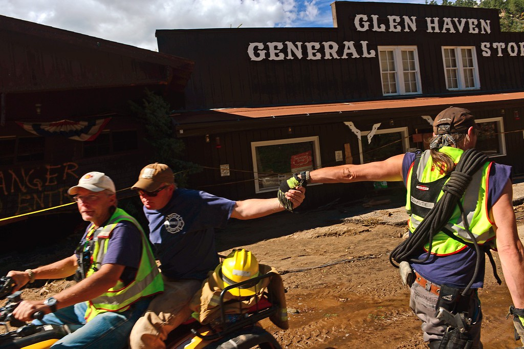 Description of . GLEN HAVEN, CO - SEPTEMBER 17:  Glen Haven Fire Captain Tom Housewright high fives a fellow firefighter as the two cross on main street of Glen Haven, CO on September 17, 2013.  (Driving the ATV is firefighter Clifton DeWitt.) The small mountain town of Glen Haven north east of Estes Park has been wiped out by the recent and massive flooding.   (Photo By Helen H. Richardson/ The Denver Post)