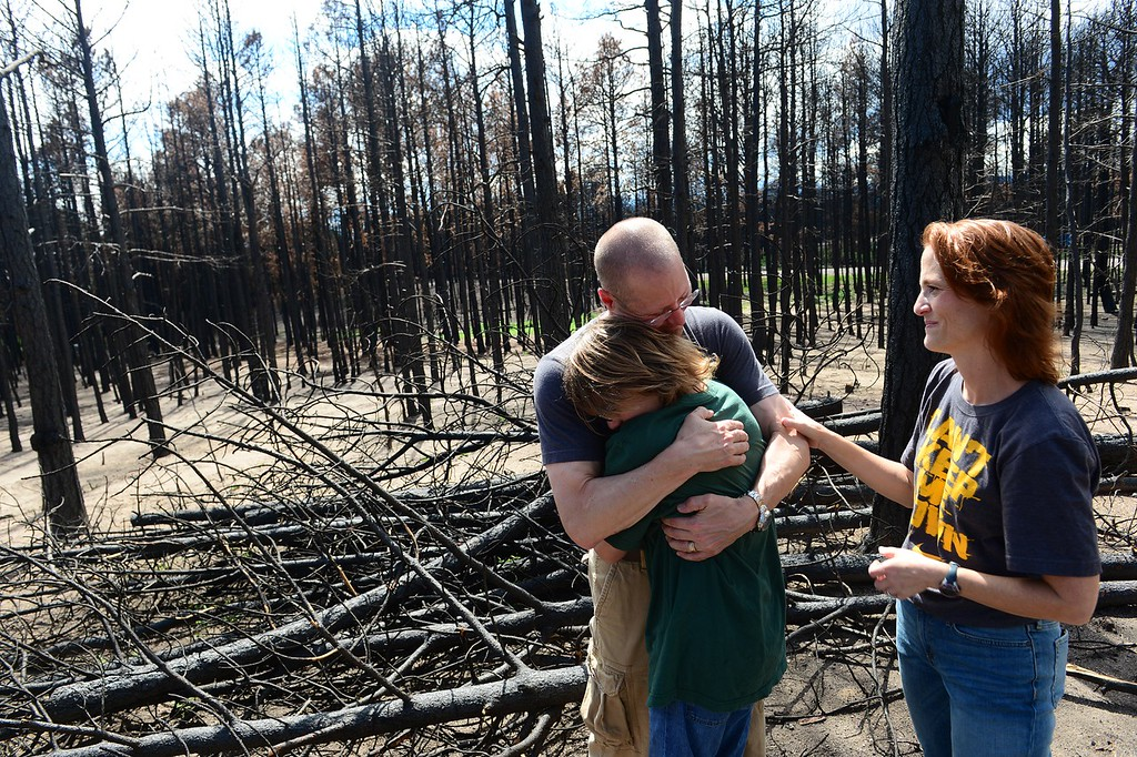 Description of . BLACK FOREST, CO - AUGUST 25:  Homeowner  Pat Hoeffel hugs his son Sam with his wife Sue Hoeffel, right, by his side on their property at 13970 Wyandotte Drive in Black Forest, CO on August 25, 2013.  The family, who had only lived there for two years, lost everything in the fire.  Luckily they were able to save their two dogs before their house burned.  The family has just hired a contractor to begin the rebuilding process.  Photo by Helen H. Richardson/The Denver Post)