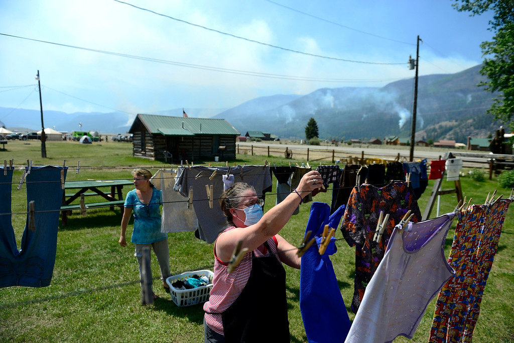 Description of . CREEDE, CO - JUNE 25: Betty Nicholopoulos wears a mask as she does laundry with Sheryl Forrester as the Papoose fire continues to burn near Creede. The three fires that make up the West Fork Complex fire now top out at more than 70 thousand acres. (Photo by AAron Ontiveroz/The Denver Post)