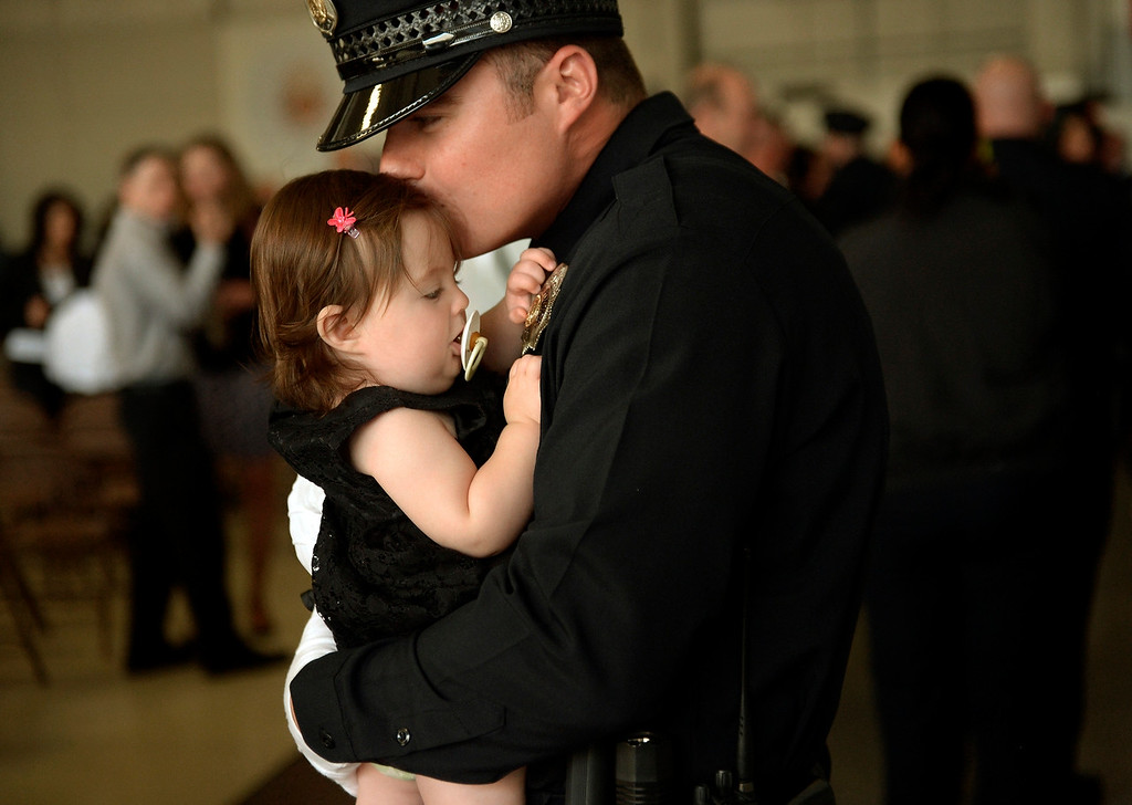 Description of . DENVER, CO. - October 23: Six month old Paisley Simmons is very interested in her father, Brendan P. Simmons, new badge after the Denver Police Department graduated recruits for the first time in five years at the Denver Police Academy. October 23, 2013 Denver, Colorado. (Photo By Joe Amon/The Denver Post)