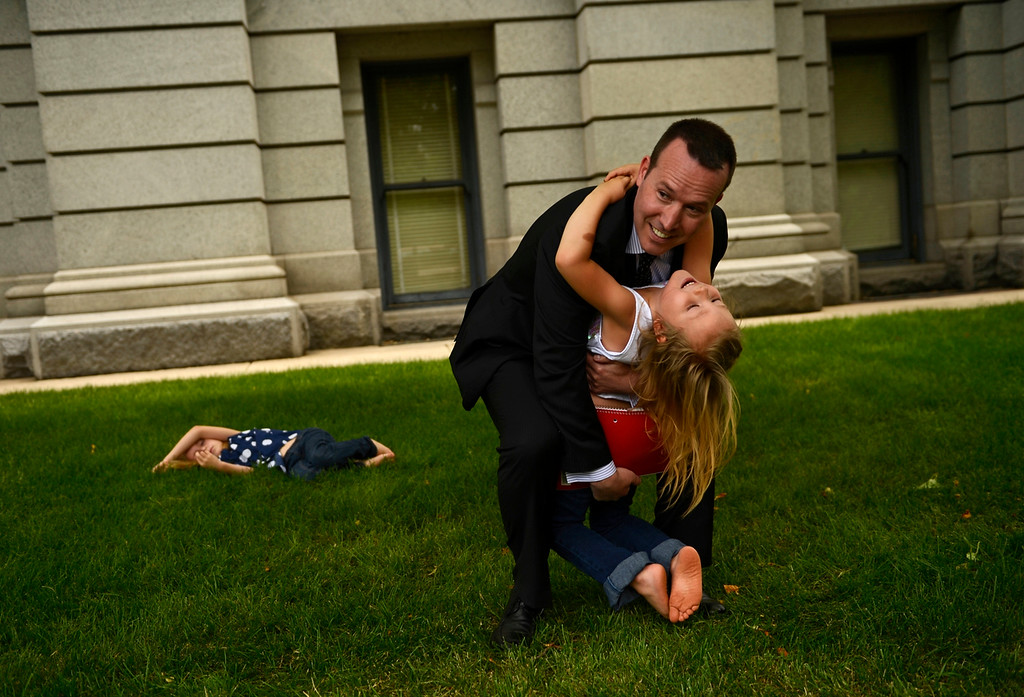 Description of . DENVER, CO-June 24, 2013: Six-year-old Coy Mathis hugs her attorney Michael Silverman outside the Colorado State Capitol after announcing that the Colorado Civil Rights Division has ruled in favor of Coy Mathis, whose school had barred her from using the girls' bathroom at her elementary school because she is transgender, June 24, 2013. Coy was labeled male at birth, but has always known that she is a girl, which she has expressed since she was 18 months old. Coy's older sister, Dakota, 9, lies in the grass behind them. (Photo By RJ Sangosti/The Denver Post)