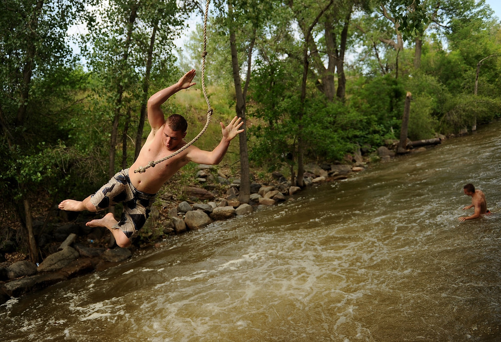 Description of . BOULDER, CO - JULY 15:   Blake Carver, 18, of Thornton, gets ready to fly into Boulder Creek off of the popular rope swing near Eben G. Fine park in Boulder, CO on July 15, 2013.  With three consecutive days of rain creeks, rivers and reservoirs are swollen with water. Photo by Helen H. Richardson/The Denver Post)