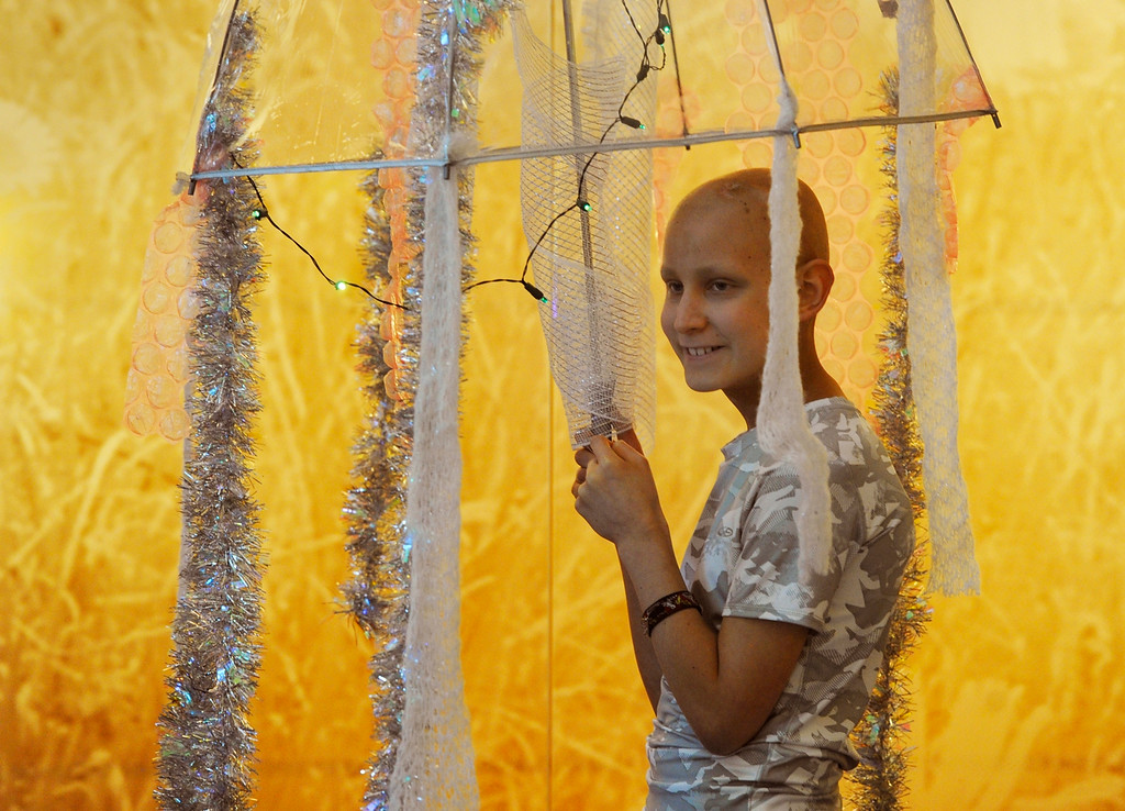 Description of . AURORA, CO - OCTOBER 31: Children's Hospital patient, Izaac Kinnison, 11, holds a clear umbrella with stands of tinsel and lights on it depicting a jelly fish during a Halloween party at Children's Hospital Colorado on the Anschutz Medical Campus in Aurora Colorado, Thursday afternoon, October 31, 2013. Earlier, hospital staffers performed a flash mob dance for patients and their families. Kinnison is fighting a brain tumor and is currently going through a round of chemotherapy at Children's, but found the strength to come to the party. (Photo By Andy Cross/The Denver Post)