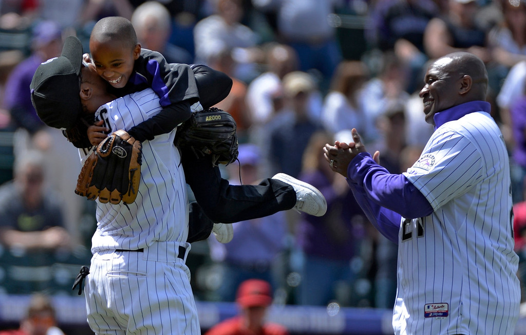Description of . DENVER, CO. - APRIL 21: Colorado Rockies retired player Eric Young (R) looks on as stands Dallas Young 6-years-old jumps in the arms of his older brother Eric Young Jr. after throwing out the first pitch prior to their game against the Arizona DiamondBacks April 21, 2013 at Coors Field. (Photo By John Leyba/The Denver Post)