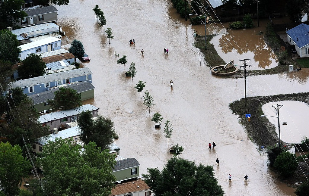 Description of . EVANS, CO. - SEPTEMBER 16:  People walk down 37th street in Evans Colorado, carrying belongings recovered from flooded  homes in the area. Aerial photographs of the Platte River flooding cities and farms in Weld County Colorado. (Photo By Tim Rasmussen/The Denver Post)