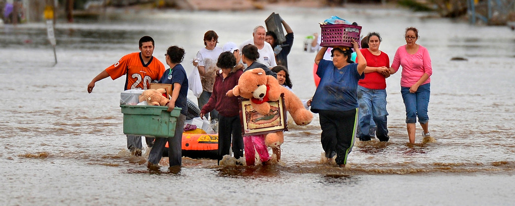 Description of . EVANS, CO - SEPTEMBER 16: Residents in Evans carry out belongings from their flooded homes, September 16, 2013. Massive flooding continues to hit Colorado. (Photo By RJ Sangosti/The Denver Post)
