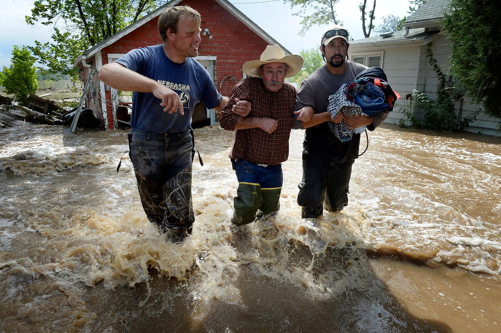 Description of . HYGIENE, CO. - SEPTEMBER 14:  Dan Hull, center, is assisted by Brian Marquedt, left, and Scott Johnson after rescuing Hull's two cats and gathering some items from his flooded home on Hygiene Road in Hygiene,  CO September 14, 2013.  (Photo By Craig F. Walker / The Denver Post)