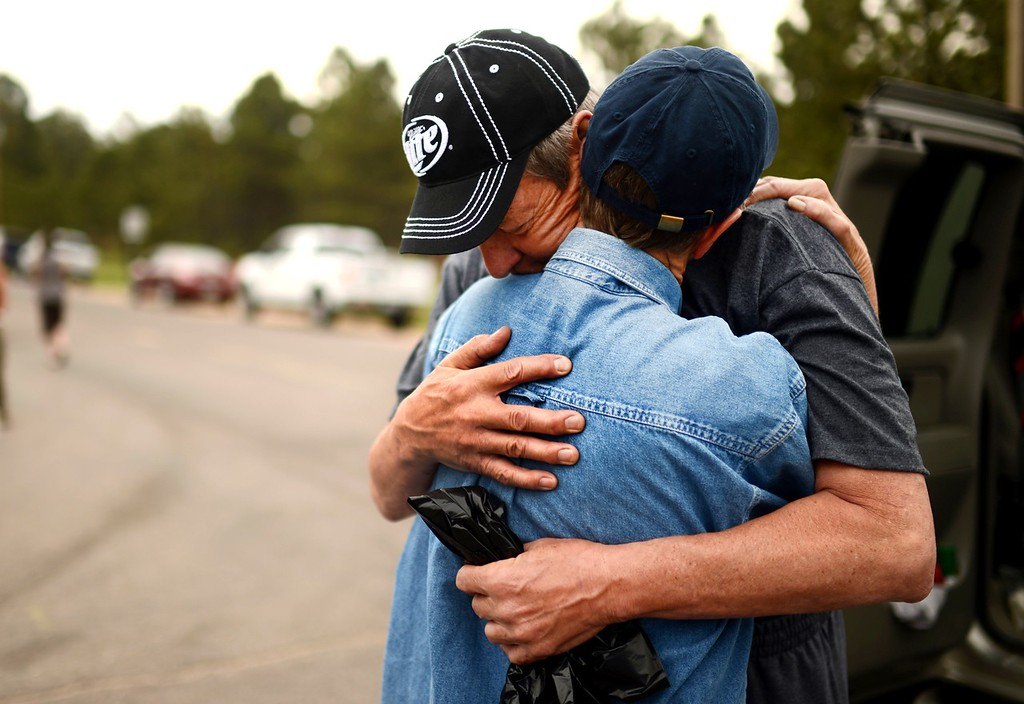 Description of . Black Forest Fire evacuees Cindy Miller, hugs her husband Ray before his going to their property with El Paso County Sheriff's escort at the corner of Vollmer Rd. and Burgess Rd, June 14, 2013. Ray went to pick up their truck. They lost their house by the fire. (Photo By Hyoung Chang/The Denver Post)