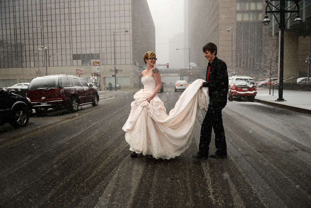 Description of . DENVER, CO-May 01, 2013: Erin Ivie, 23, left, and her partner Kristyn Lindstrom, 25, leave to do wedding photos, outside in the snow, after their civil-union  ceremony in downtown Denver, May 01, 2013.  Hundreds of Colorado gay and lesbian couples put an official government seal on their relationships. (Photo By RJ Sangosti/The Denver Post)