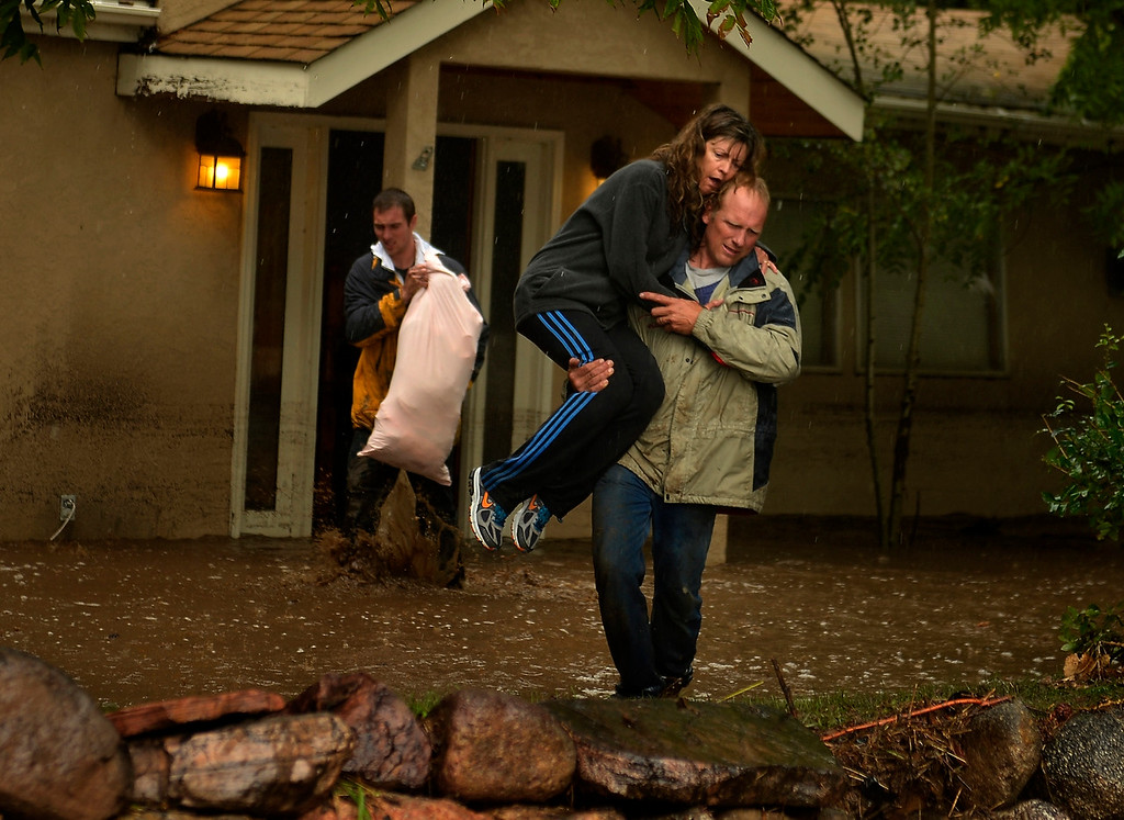 Description of . BOULDER, CO. - September 12: Kyle Schuler trudges through the water and mud as Cheryl Schuler is carried from her home by her husband Kim after being at their home on Upland Ave to salvage what they can when heavy overnight rains flooded 4 Mile Creek in Boulder September 12, 2013 Boulder, Colorado. (Photo By Joe Amon/The Denver Post)