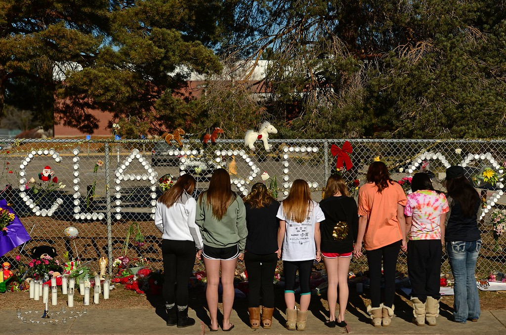 Description of . CENTENNIAL, CO - DECEMBER 17, 2013: Members of the Arapahoe High School cheerleading squad came to leaves notes, flowers and  their prayers for shooting victim Claire Davis at a tribute for her on a fence outside the school along Dry Creek road  in Centennial, CO on December 17, 2013. Davis remains in critical but stable condition in a coma at Littleton Adventist Hospital.  (Photo By Helen H. Richardson/ The Denver Post)