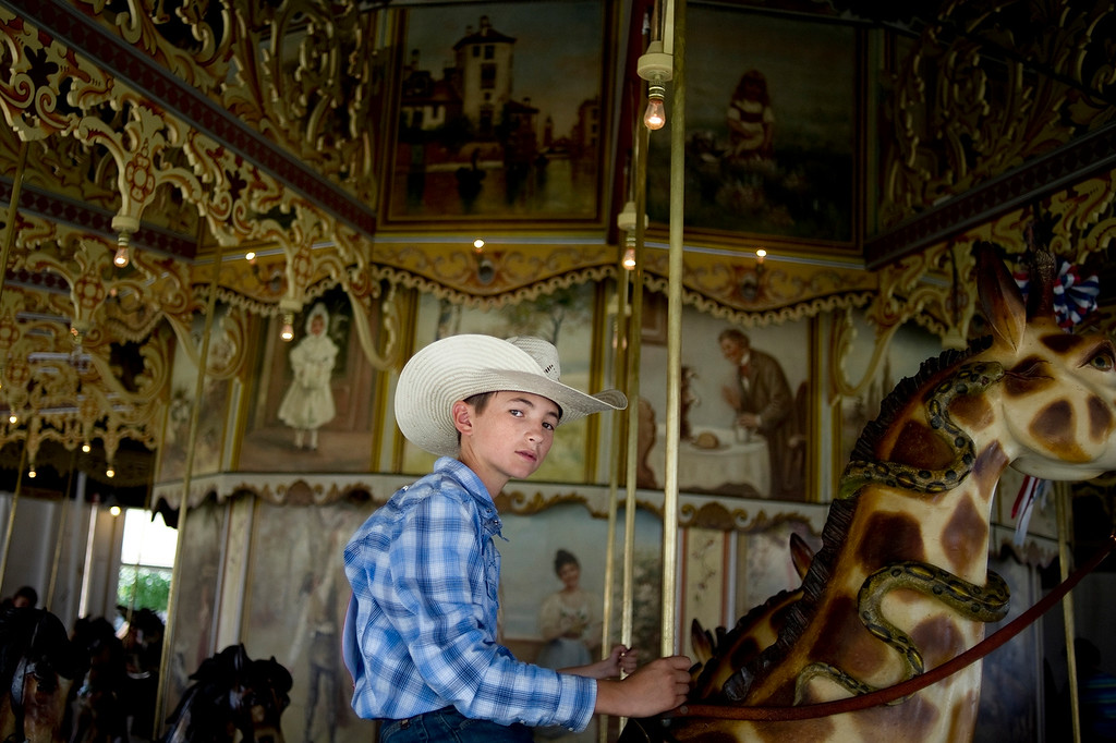 Description of . BURLINGTON, CO - AUGUST 09, 2013: Jace Roselle, 13, rides a snake-wrapped giraffe on the Kit Carson County Carousel during a break between competitions at the neighboring rodeo in Burlington, Co. (Photo By Grant Hindsley/The Denver Post)