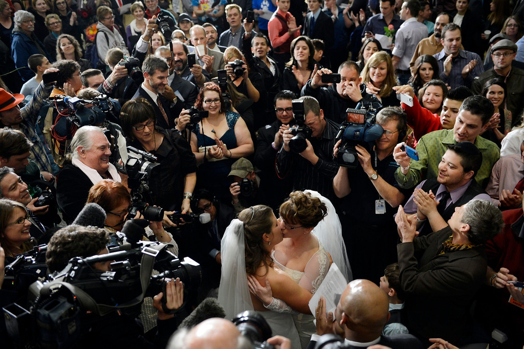 Description of . DENVER, CO. - MAY 01: Lead by Mayor Michael Hancock, Anna and Fran Simon are the first couple to take part in a civil union ceremony at the Webb Building in  Denver CO, May 01, 2013.  The Clerk and Recorder's Office opened for business from midnight to 3 a.m. to issue civil union licenses to couples on May 01, 2013 when the Civil Union Act became law. One Colorado offered a civil-union celebration for couples in the building's atrium from midnight to 2 a.m., as judges, magistrates and other officiants performed the ceremonies. Colorado became the latest state to recognize the legal rights of same-sex couples — through marriage or civil unions — when Gov. John Hickenlooper signed state Senate Bill 11 into law March 21. (Photo By Craig F. Walker/The Denver Post)