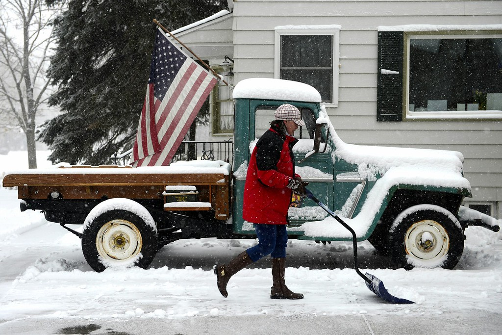 Description of . DENVER, CO - FEBRUARY 24: Nikki Maloney shovels snow in front of a 1962 Willys truck at her home on Monroe in south Denver. Snow is expected to fall throughout the day. (Photo by AAron Ontiveroz/The Denver Post)