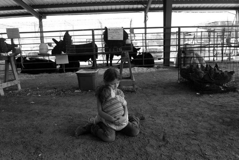 "Description of  LAMAR, CO-August, 2013: Eight-year-old Jaden Kalma helps her mother by holding her baby sister, Jerney, 1, during a nap at the Prowers County Sand and Sage Fair, August 08, 2013. Their mother, Kerry Kalma, was busy helping their other sister show lambs. ""We all have to help out. That's how people around here survive ... we all need to do our part,"" said Kerry."