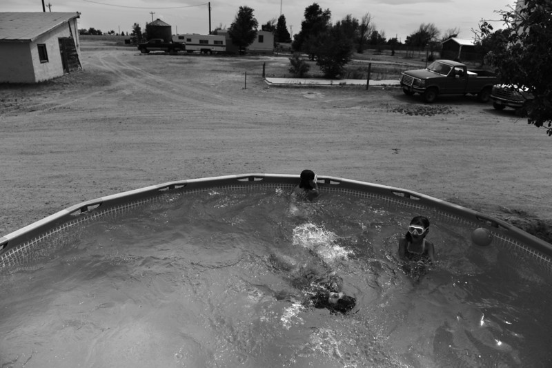 Description of  HASWELL, CO - JUNE 22: Children in the Briggs family cool off in a pool outside their home in Haswell, June 22, 2013. The pool is like an oasis in Haswell, hit hard by the drought, as neighborhood children often stop by for a dip.