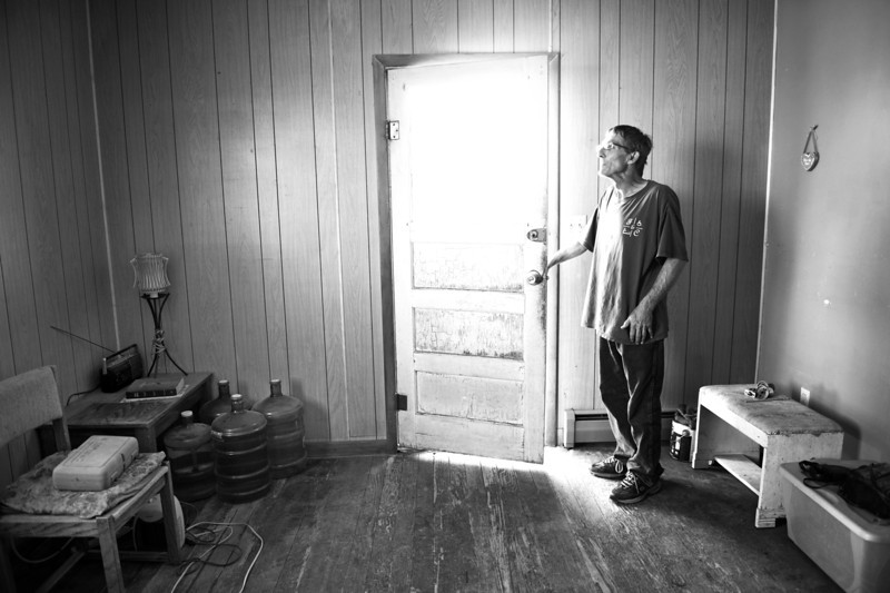 Description of  WILD HORSE, CO-June 23, 2013: Bill Skinner opens the front door of his home in Wild Horse, CO, June 23, 2013. Skinner said there are two things you need to live in this country, which he keeps by his front door -- water and the Bible. (Photo By RJ Sangosti/The Denver Post)