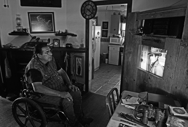 "Description of  KARVAL, CO-July 25, 2013: Joseph Eaglefeather watches westerns at his home in Karval, CO, July 25, 2013. Eaglefeather was hurt in a car crash and received financial assistance due to the accident. ""Without that money, there is no way I could stay here. I feel sorry for people around here. There is no money or work to be found,"" he said, referring to the town that he loves. (Photo By RJ Sangosti/The Denver Post)"