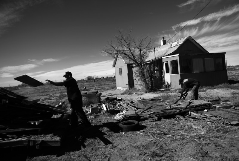Description of  SUGAR CITY, CO - NOVEMBER 04: Nathan Vaisa, left, and Harry Tomlin clean up around an abandoned home in Sugar City, November 04, 2013. The two work for a local bank that will try to auction off the property.