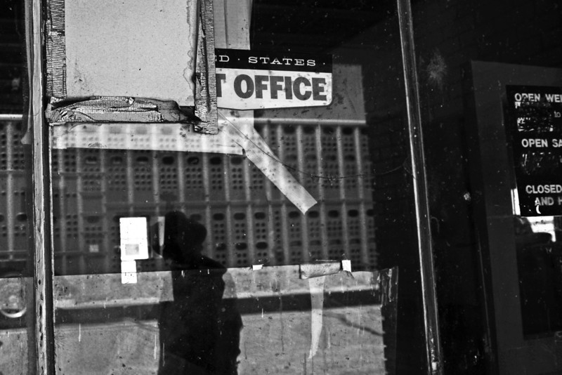 "Description of  BRISTOL, CO - JULY 23, 2013: Elmer Stalford's shadow is seen in the window of the closed post office in Bristol as he turns to look at a cattle truck passing through town, July 23, 2013. Stalford runs the only still operating business in Bristol - an auto repair shop. ""I am the only business left. They have all moved on,"" he said. Bristol lost its township after the post office closed."