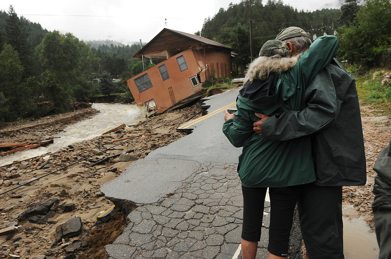 Jamestown resident Colleen Williams gives her neighbor Leon Hill, right, a hug early in the morning along James Canyon drive in Jamestown, CO on September 15, 2013. The town has been completely destroyed from the recent floods. A dozen or so residents stayed as most of the town was evacuated by helicopters. (Photo By Helen H. Richardson/ The Denver Post)