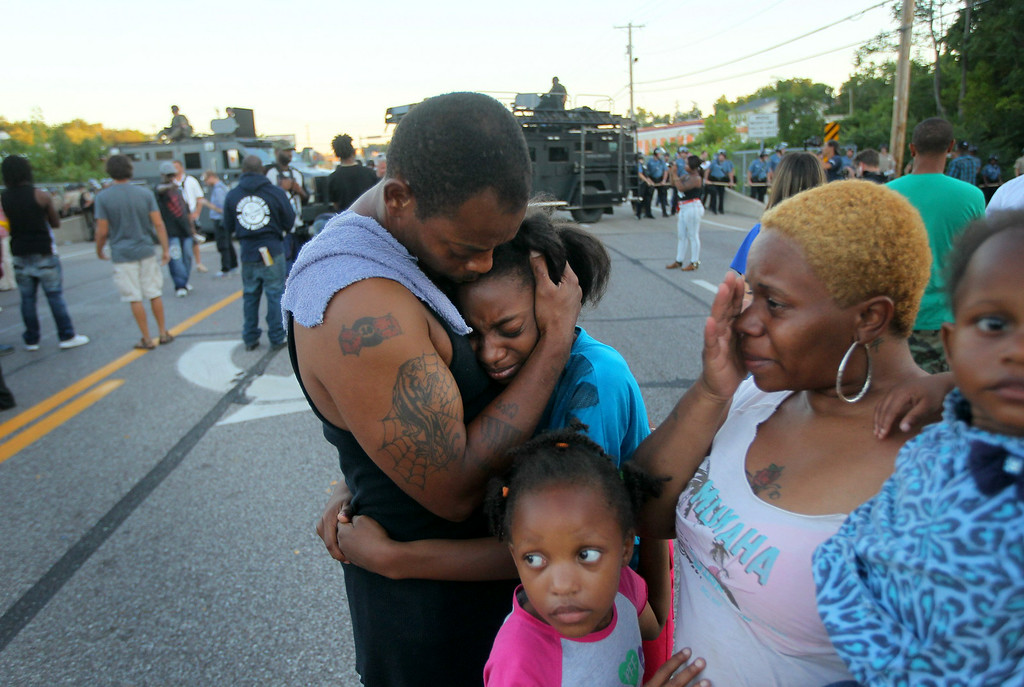 Description of . Terrell Williams El hugs his daughter Sharell, 9, while standing with his wife, Shamika Williams, and daughters Tamika, 6, and Sharell, 2, on Wednesday, Aug. 13, 2014, in Ferguson, Mo. (AP Photo/St. Louis Post-Dispatch, David Carson)