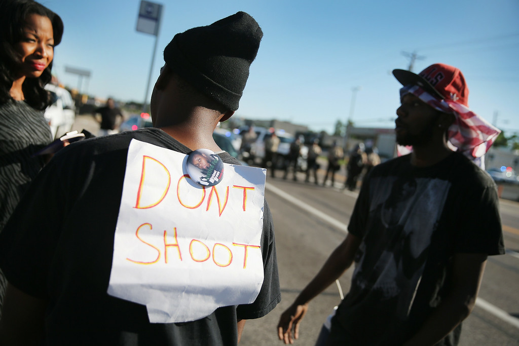 Description of . FERGUSON, MO - AUGUST 13:  Demonstrators protest the shooting death of teenager Michael Brown on August 13, 2014 in Ferguson, Missouri. Brown was shot and killed by a Ferguson police officer on Saturday. Ferguson, a St. Louis suburb, has experienced three days of violent protests since the killing.  (Photo by Scott Olson/Getty Images)