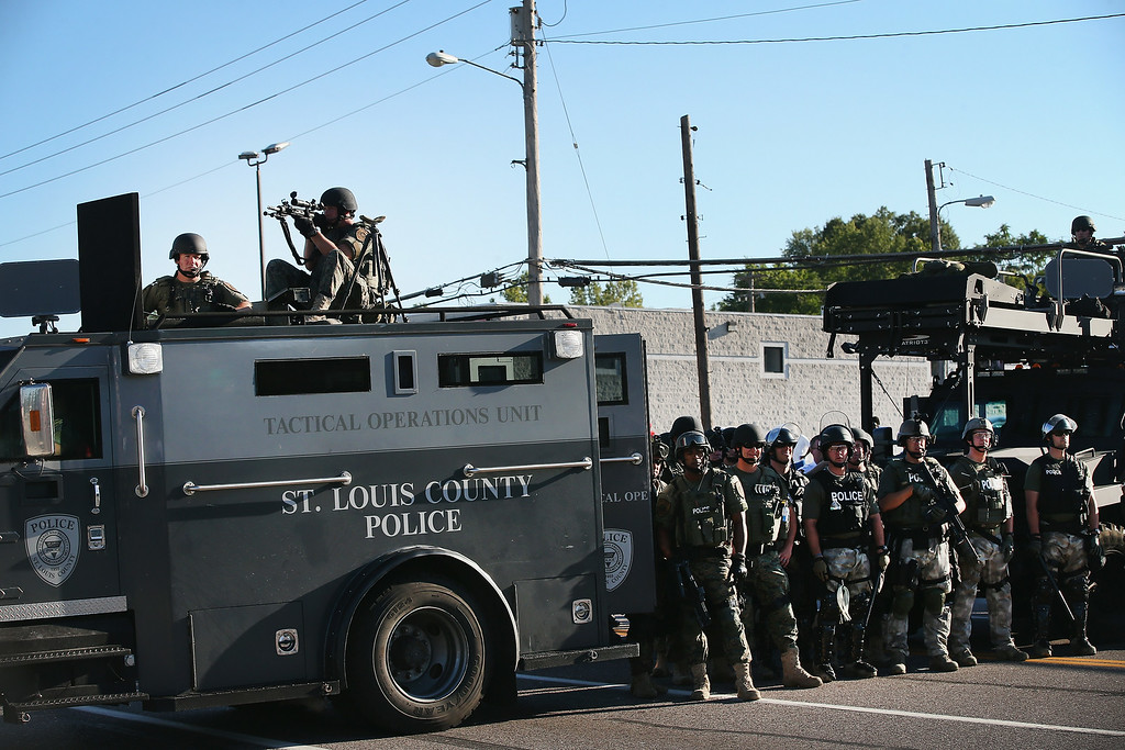 Description of . Police stand watch as demonstrators protest the shooting death of teenager Michael Brown on August 13, 2014 in Ferguson, Missouri. Brown was shot and killed by a Ferguson police officer on Saturday. Ferguson, a St. Louis suburb, is experiencing its fourth day of violent protests since the killing.  (Photo by Scott Olson/Getty Images)