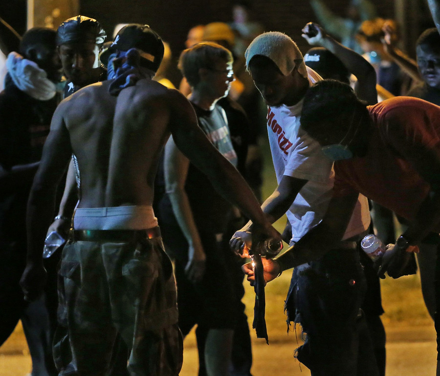 Description of . Protesters try unsuccessfully to light a Molotov cocktail, Wednesday, Aug. 13, 2014, in Ferguson, Mo. Protests in the St. Louis suburb rocked by racial unrest since a white police officer shot an unarmed black teenager to death turned violent Wednesday night, with people lobbing molotov cocktails at police who responded with smoke bombs and tear gas to disperse the crowd. (AP Photo/St. Louis Post-Dispatch, Chris Lee)