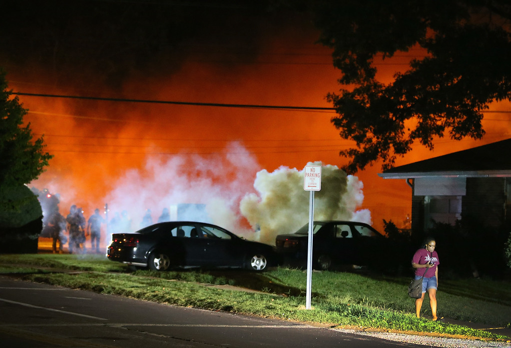 Description of . A young woman walks from a corner after police standing near the corner fired tear gas at her on August 13, 2014 in Ferguson, Missouri. Ferguson is experiencing its fourth day of unrest after following the shooting death of teenager Michael Brown on Saturday. Brown, who was not armed was shot and killed by a Ferguson police officer. (Photo by Scott Olson/Getty Images)