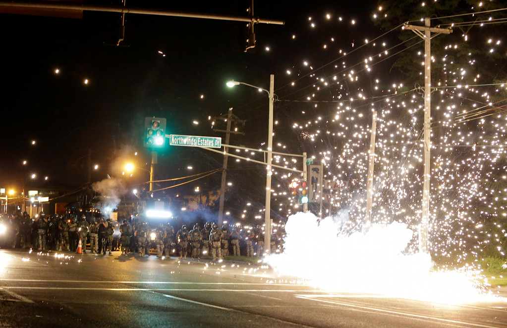 Description of . A device deployed by police goes off in the street as police and protesters clash Wednesday, Aug. 13, 2014, in Ferguson, Mo. Authorities in the St. Louis suburb where an unarmed black teen was shot and killed by a police officer have used tear gas to try to disperse protesters after flaming projectiles were thrown from the crowd. (AP Photo/Jeff Roberson)