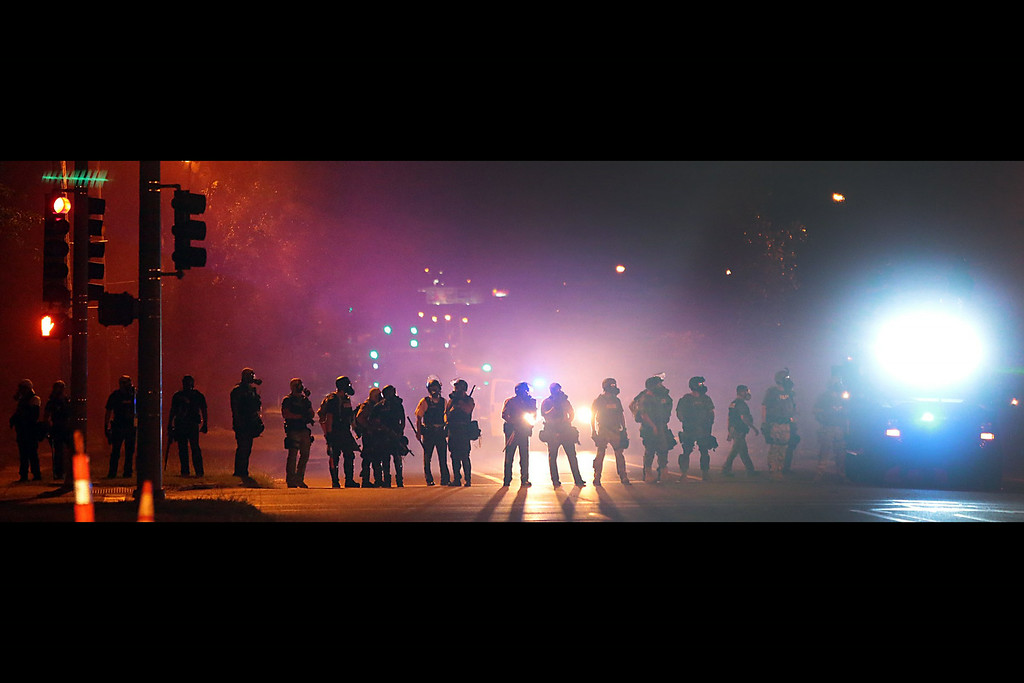 Description of . Police officers work their way north on West Florissant Avenue in Ferguson, Mo., clearing the road of people Wednesday, Aug. 13, 2014.  (AP Photo/St. Louis Post-Dispatch, Robert Cohen)