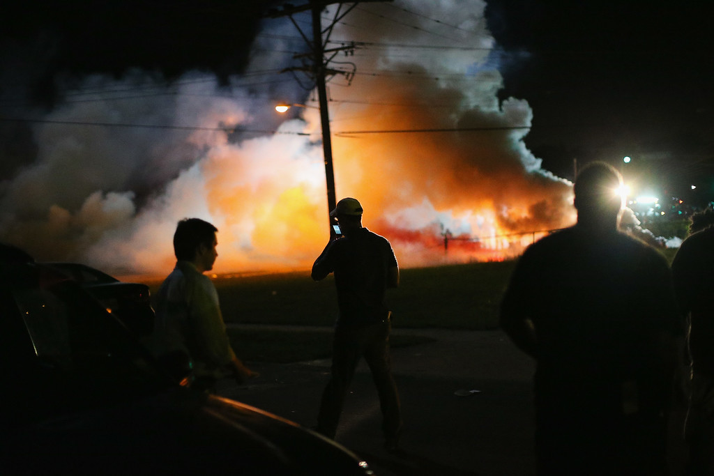Description of . Demonstrators, protesting the shooting death of teenager Michael Brown, scramble for cover as police fire tear gas on August 13, 2014 in Ferguson, Missouri. Brown was shot and killed by a Ferguson police officer on Saturday. Ferguson, a St. Louis suburb, is experiencing its fourth day of violent protests since the killing.  (Photo by Scott Olson/Getty Images)