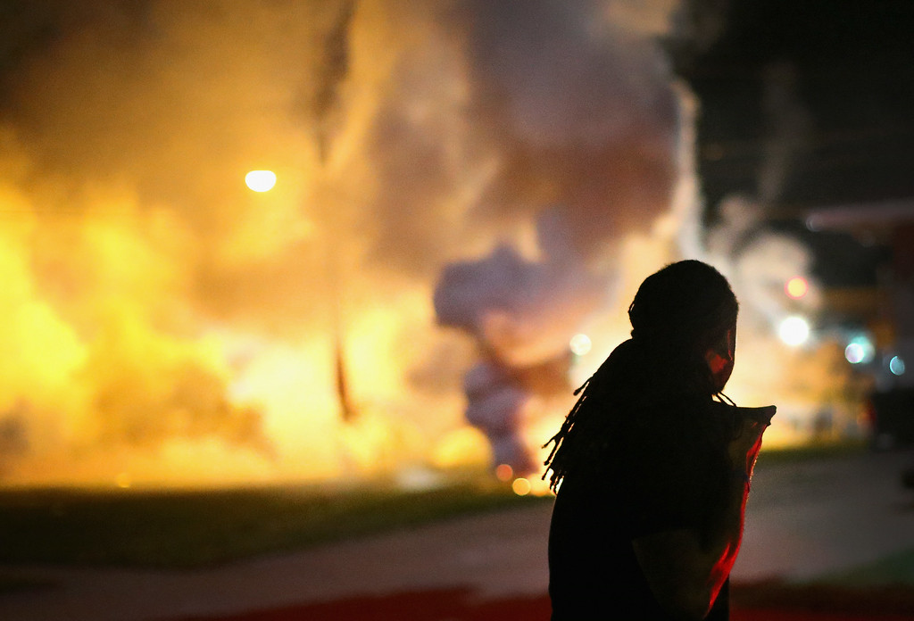 Description of . A demonstrator, protesting the shooting death of teenager Michael Brown, scrambles for cover as police fire tear gas on August 13, 2014 in Ferguson, Missouri. Brown was shot and killed by a Ferguson police officer on Saturday. Ferguson, a St. Louis suburb, is experiencing its fourth day of violent protests since the killing.  (Photo by Scott Olson/Getty Images)