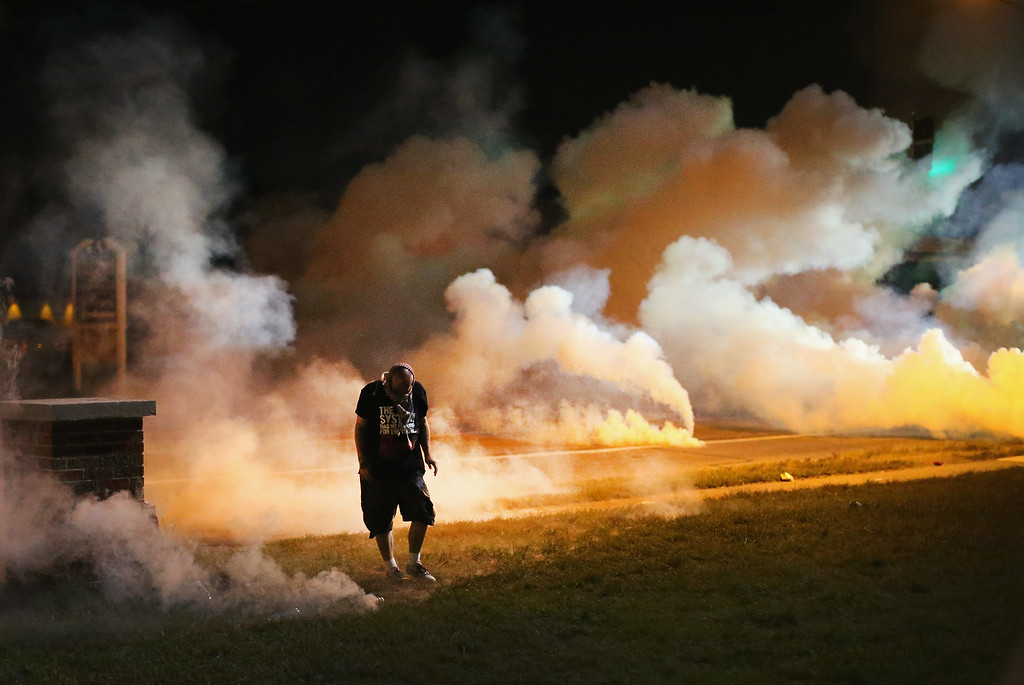 Description of . Demonstrators, protesting the shooting death of teenager Michael Brown, flee as police shoot tear gas into the crowd of several hundred after someone reportedly threw a bottle at the line of police on August 13, 2014 in Ferguson, Missouri. Brown was shot and killed by a Ferguson police officer on Saturday. Ferguson, a St. Louis suburb, is experiencing its fourth day of violent protests since the killing.  (Photo by Scott Olson/Getty Images)