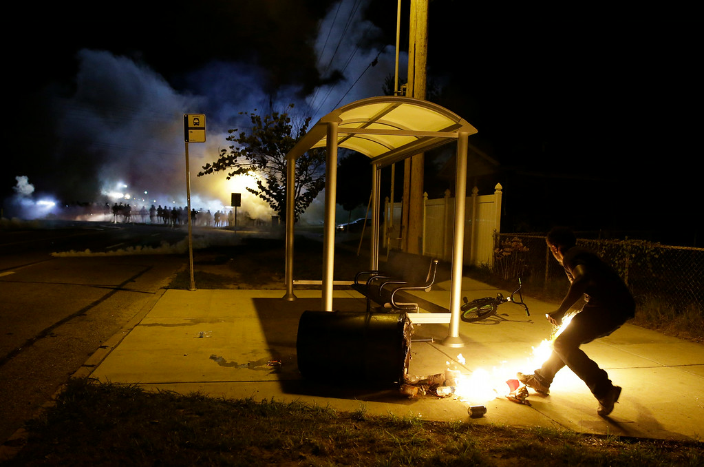 Description of . A man picks up a flaming bottle and prepares to throw it as a line of police advance in the distance Wednesday, Aug. 13, 2014, in Ferguson, Mo.  Protests in the St. Louis suburb rocked by racial unrest since a white police officer shot an unarmed black teenager to death turned violent Wednesday night, with people lobbing molotov cocktails at police who responded with smoke bombs and tear gas to disperse the crowd.  (AP Photo/Jeff Roberson)