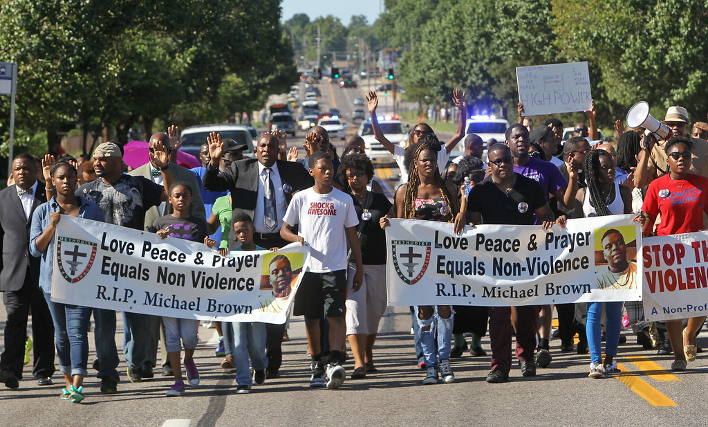 Description of . A march organized by area ministers makes its way down W. Florissant in Ferguson, Mo. on Wednesday, Aug. 13, 2014. On Saturday, Aug. 9, 2014, a white police officer fatally shot Michael Brown, an unarmed black teenager, in the St. Louis suburb. (AP Photo/St. Louis Post-Dispatch, J.B. Forbes)