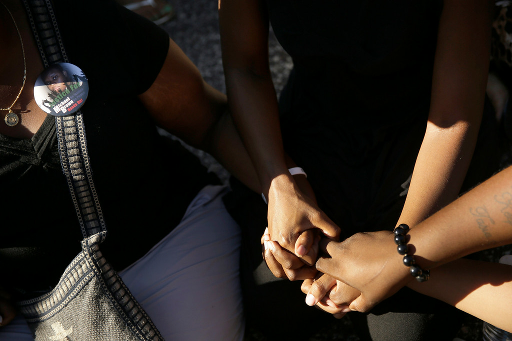 Description of . Protesters sit in the middle of a street holding hands as Missouri state Sen. Maria Chappelle-Nadal at left, wears a button remembering Michael Brown, Wednesday, Aug. 13, 2014, in Ferguson, Mo. Nights of unrest have vied with calls for calm in a St. Louis suburb where Michael Brown, unarmed black teenager was killed by police, while the community is still pressing for answers about the weekend shooting. (AP Photo/Jeff Roberson)