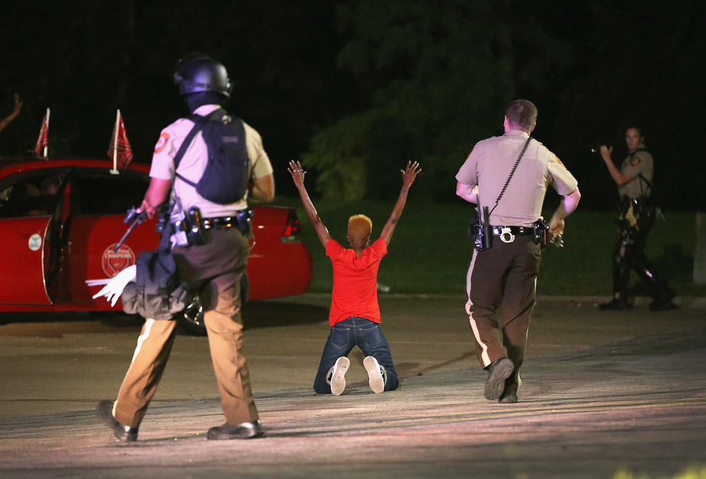 Description of . Police surround and detain two people in a car on August 13, 2014 in Ferguson, Missouri.  (Photo by Scott Olson/Getty Images)