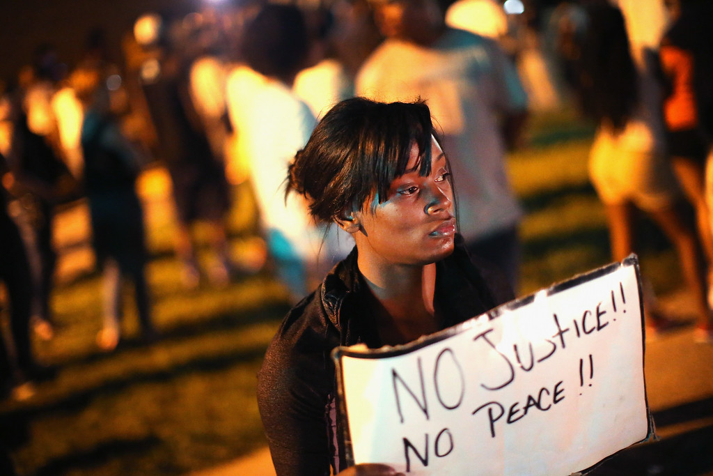 Description of . ST. LOUIS, MO - AUGUST 12:  Demonstrators protest the killing of teenager Michael Brown outside Greater St. Marks Family Church while Browns family along with civil rights leader Rev. Al Sharpton and a capacity crowd of guests met inside to discuss the killing on August 12, 2014 in St Louis, Missouri. Brown was shot and killed by a police officer on Saturday in the nearby suburb of Ferguson. Ferguson has experienced two days of violent protests since the killing but, tonight the town remained mostly peaceful.  (Photo by Scott Olson/Getty Images)