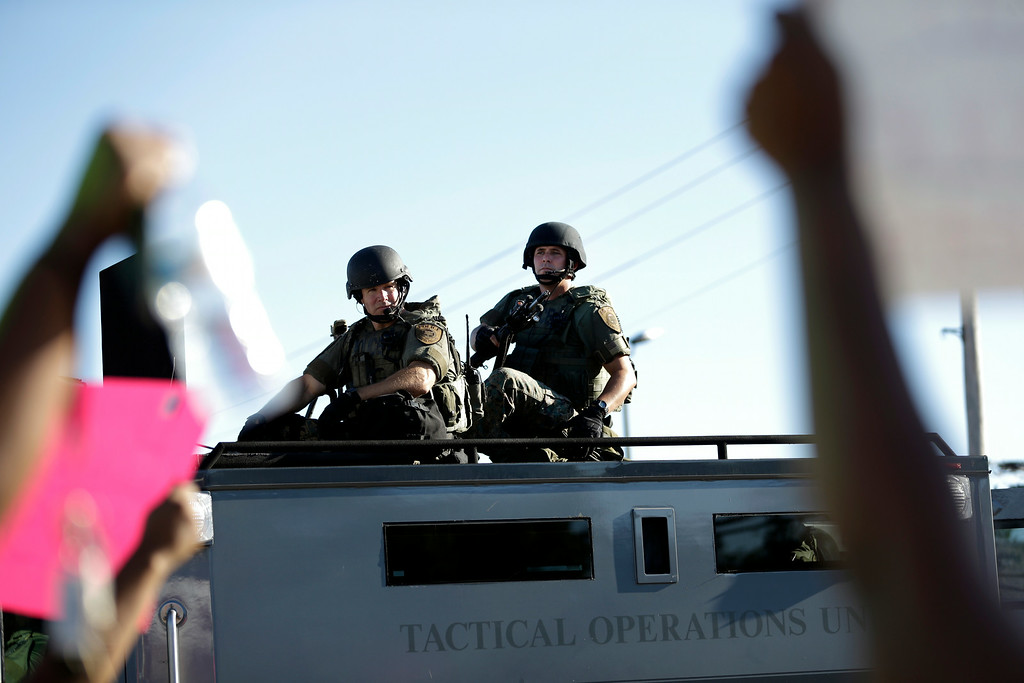 Description of . Police in riot gear watch protesters in Ferguson, Mo. on Wednesday, Aug. 13, 2014. On Saturday, Aug. 9, 2014, a white police officer fatally shot Michael Brown, an unarmed black teenager, in the St. Louis suburb. (AP Photo/Jeff Roberson)