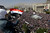 FILE - A supporter of Syrian President Bashar Assad waves a Syrian flag as she looks over a crowd gathered to show support for their president in Damascus, Syria, Tuesday, March 29, 2011. (AP Photo/Bassem Tellawi, File)
