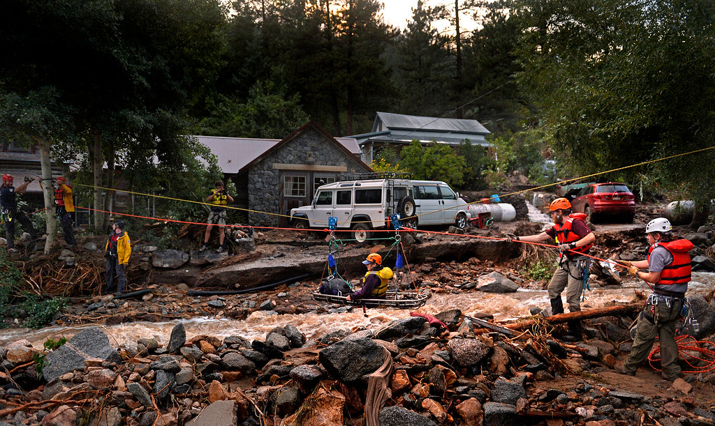 Description of . The Alpine Rescue Team uses a high line and a sling stretched across Four Mile Canyon to rescue Darian Shaw from her Salina home. Shaw and three neighbors were brought across the rushing water. The Alpine Rescue Team, Four Mile Fire and Rocky Mountain Rescue Team worked to get people out after heavy rains caused flash flooding and washed away most of the town.