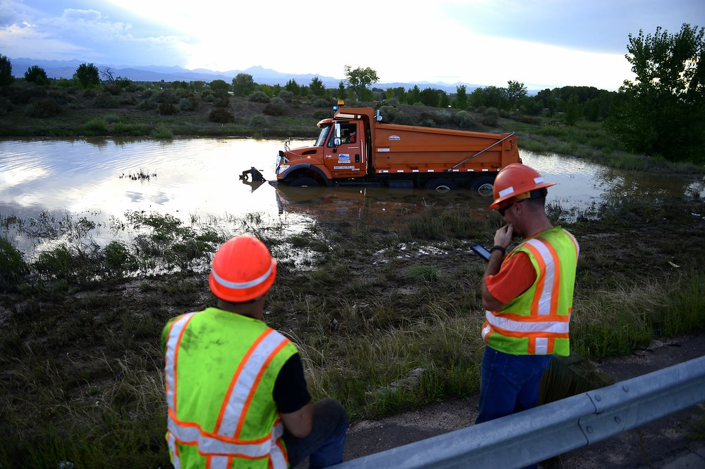 Description of . LONGMONT, CO - SEPTEMBER 17: A CDOT truck is submerged in water after blowing a tire and driving off road into a pool of flood water. CDOT employees on the scene provided no further information. (Photo by AAron Ontiveroz/The Denver Post