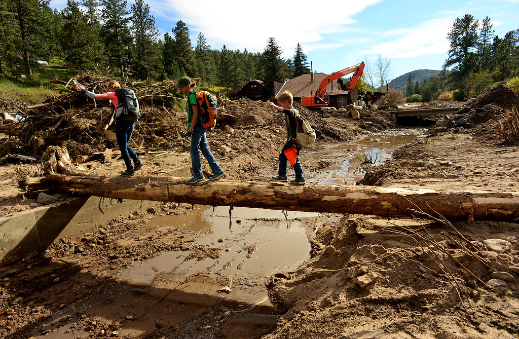 Description of . GLEN HAVEN, CO - SEPTEMBER 30: Lauren Discher, 14, and her siblings Lexie, 11, and Drew, 7, carefully cover a tree above the muddy river bed of West Creek river in Glen Haven, Co on September 30, 2013 as an excavator clears rocks, trees and debris from a culvert. The Discher family came all the way from College Station, Texas just to help clean what they could in the town and help residents in any way they could. (Photo By Helen H. Richardson/ The Denver Post)