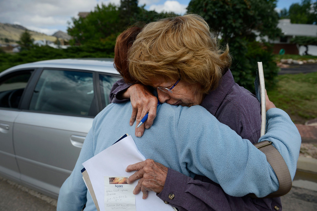 Description of . BOULDER, CO - SEPTEMBER 14: Evacuated Jamestown Colorado residents, Maggie Fitzgerald, left, and Jan Dorsey, right, embrace on September 16, 2013 near the intersection of Lee Hill Drive and 5th St. in Boulder Colorado. Both met with a FEMA official at the intersection to get much needed assistance after their town suffered heavy damage in the flood. (Photo By Andy Cross/The Denver Post)